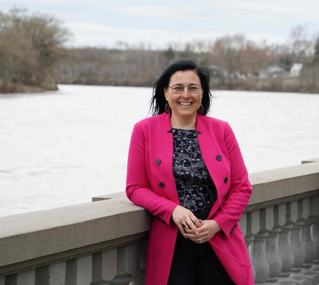 Marijo Demers souriante, au Jardin des Anciens Maires, adossée à une rambarde, posée devant la rivière Yamaska.